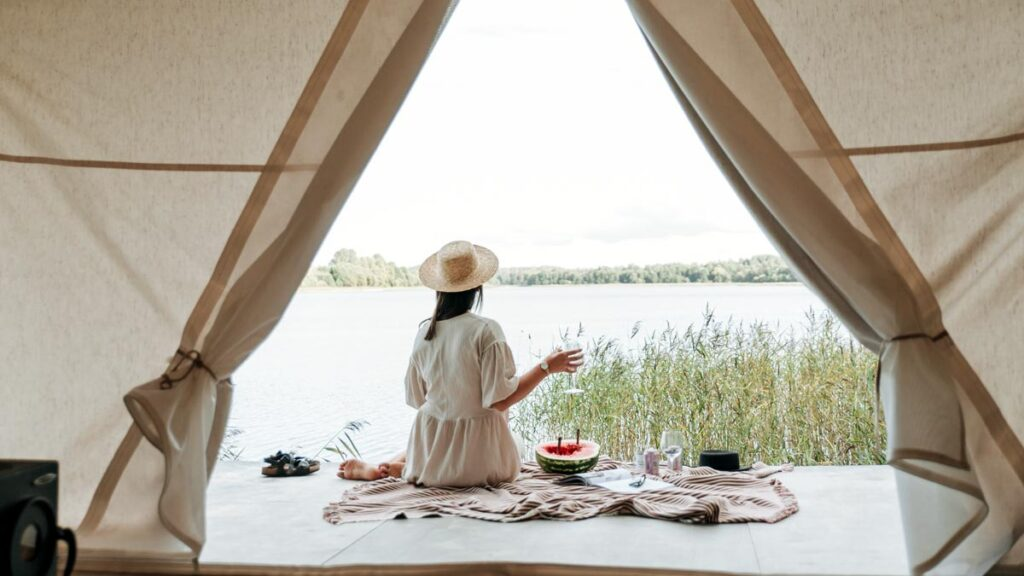 A woman site with breakfast outside a tent while glamping vs camping