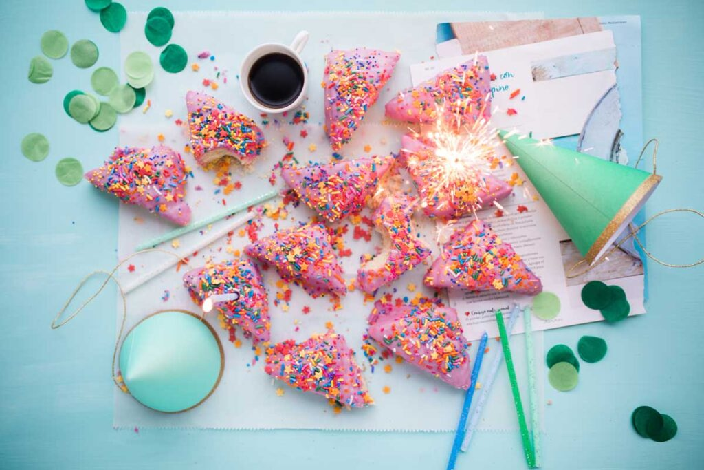 Donuts and party hats spread in a flatlay on the office table