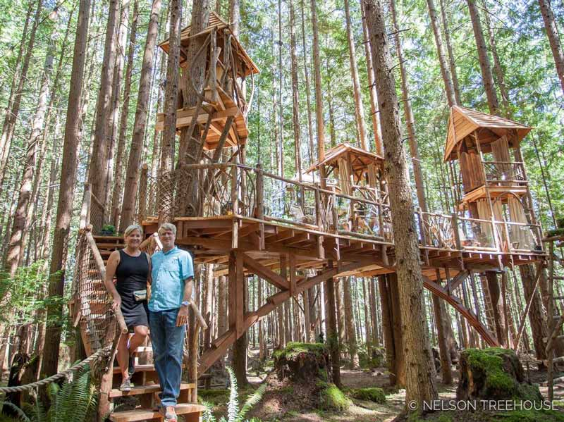 Judy and Pete stand in front of one of their treehouses from the Nelsons' camping blogs