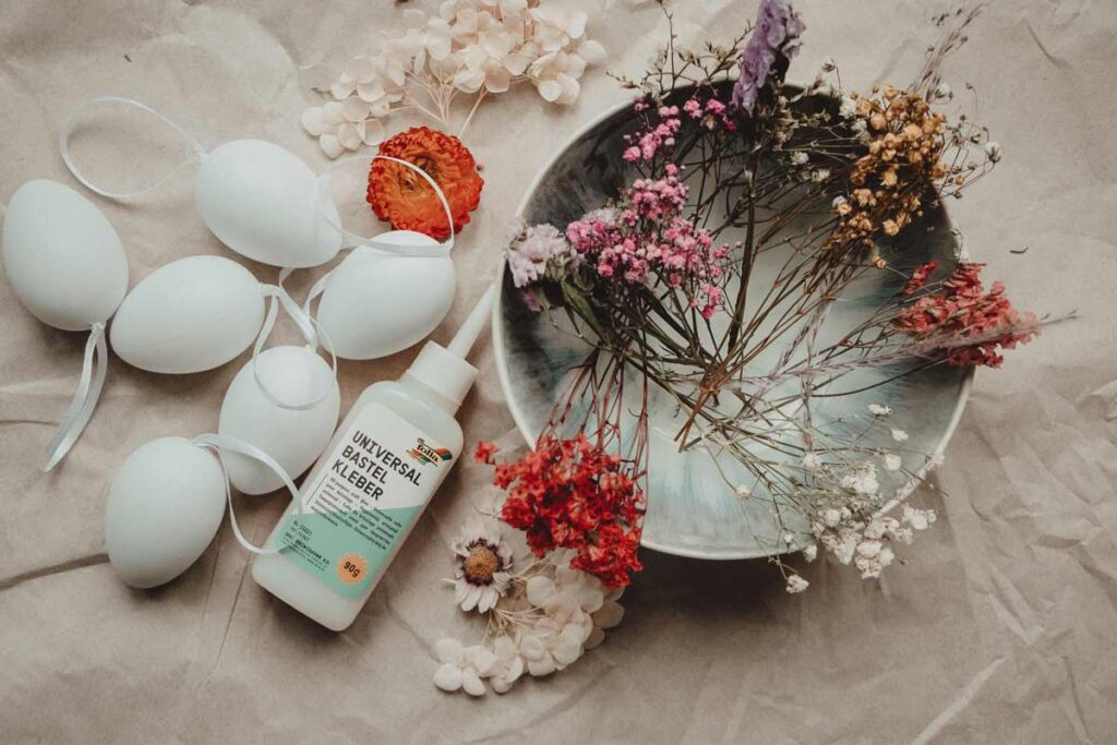 5 white eggs lie next to glue and a bowl full of flowers as the main items you need for this Easter egg DIY