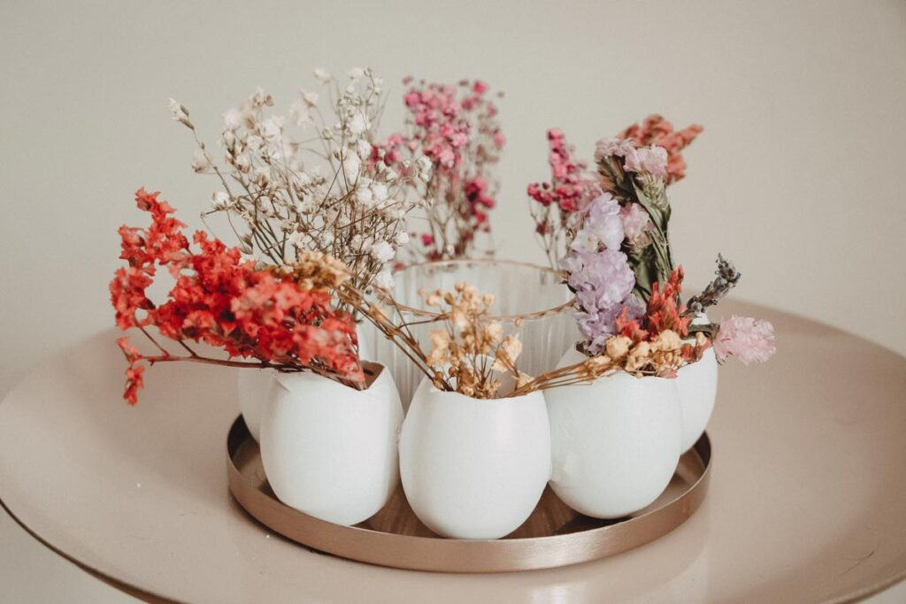 A DIY Easter wreath creation made up on a circle of eggs and used as vases with flowers in them.