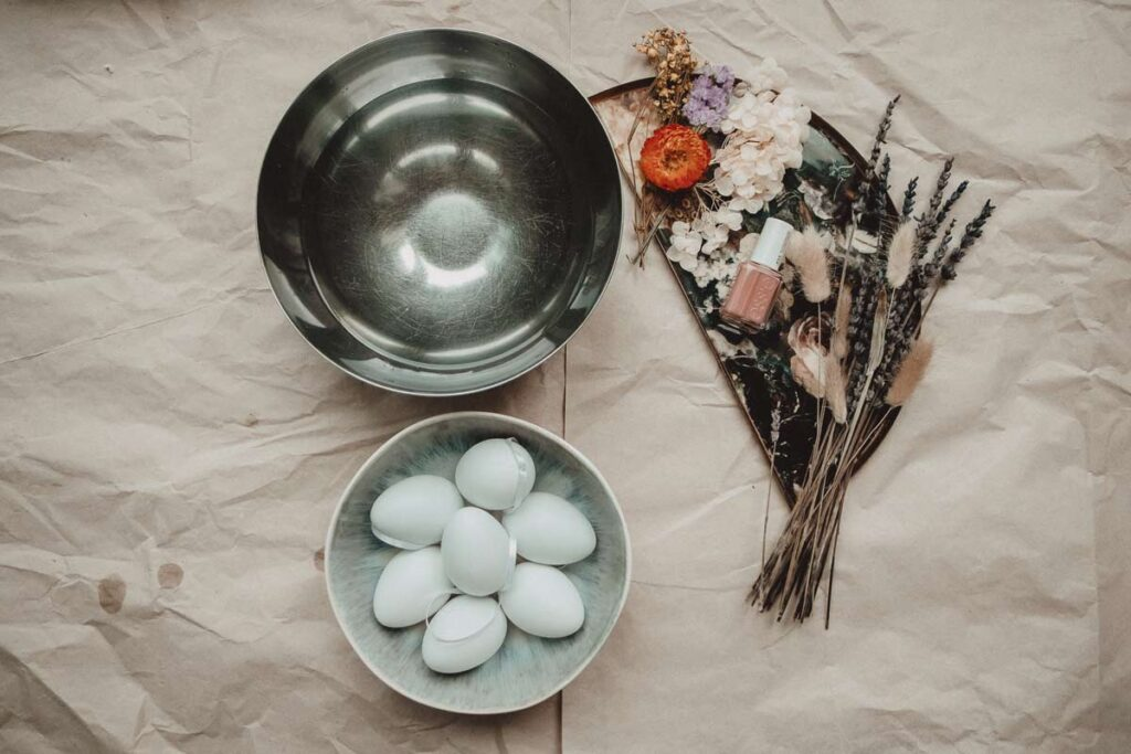 A flat lay view of a bowl of water next to a bowl of Easter eggs and a bunch of dried flowers