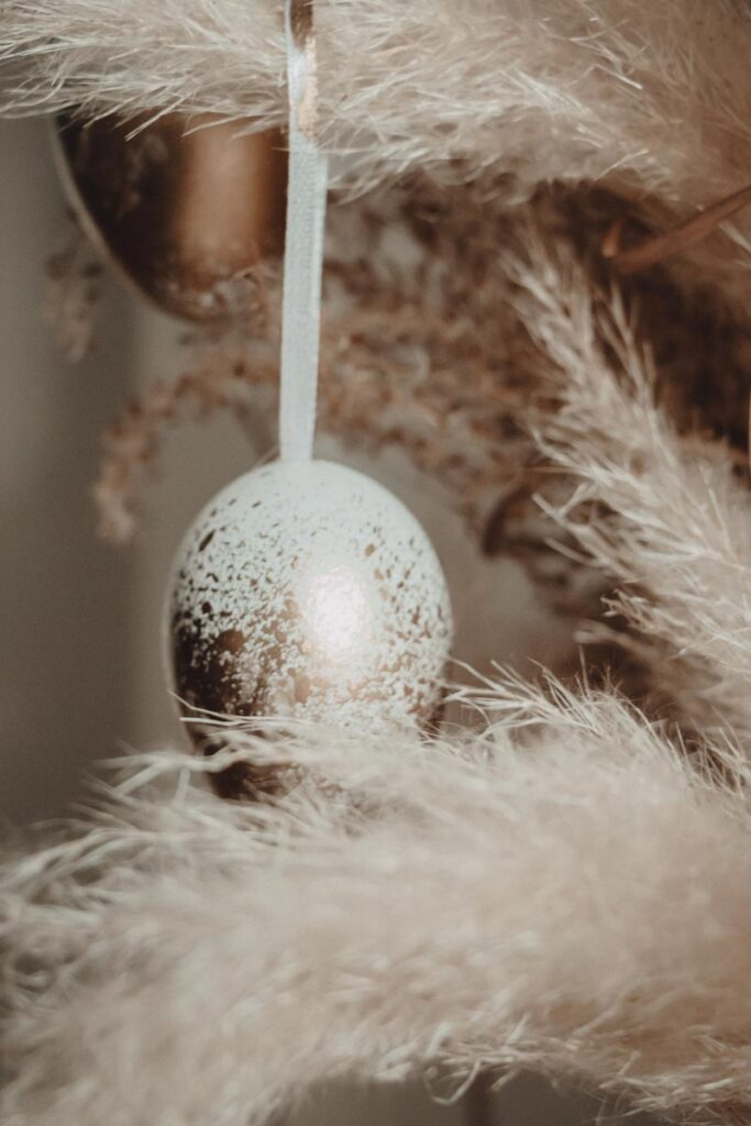 An DIY ombre Easter egg creation hanging from a tree