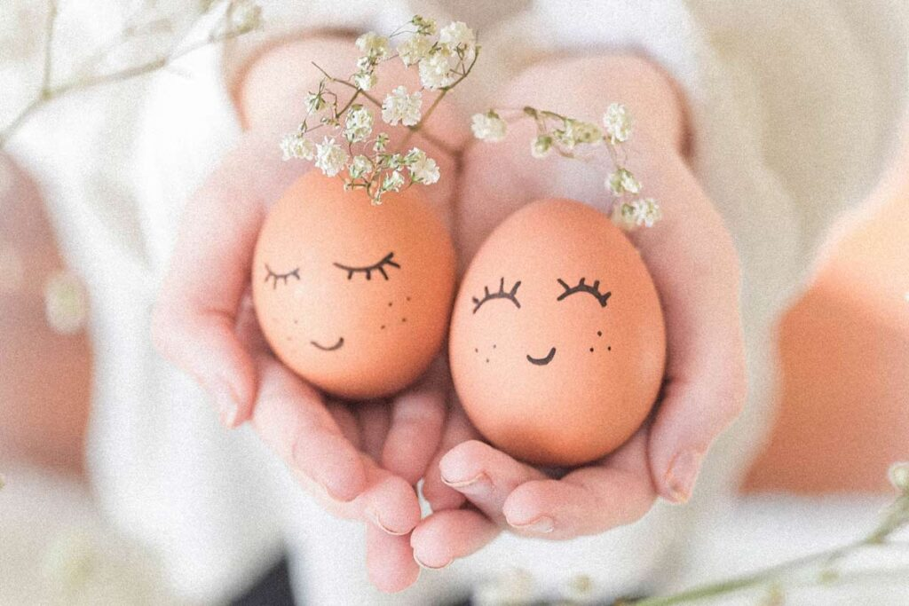 Two eggs with smily faces drawn on held in someone's hands