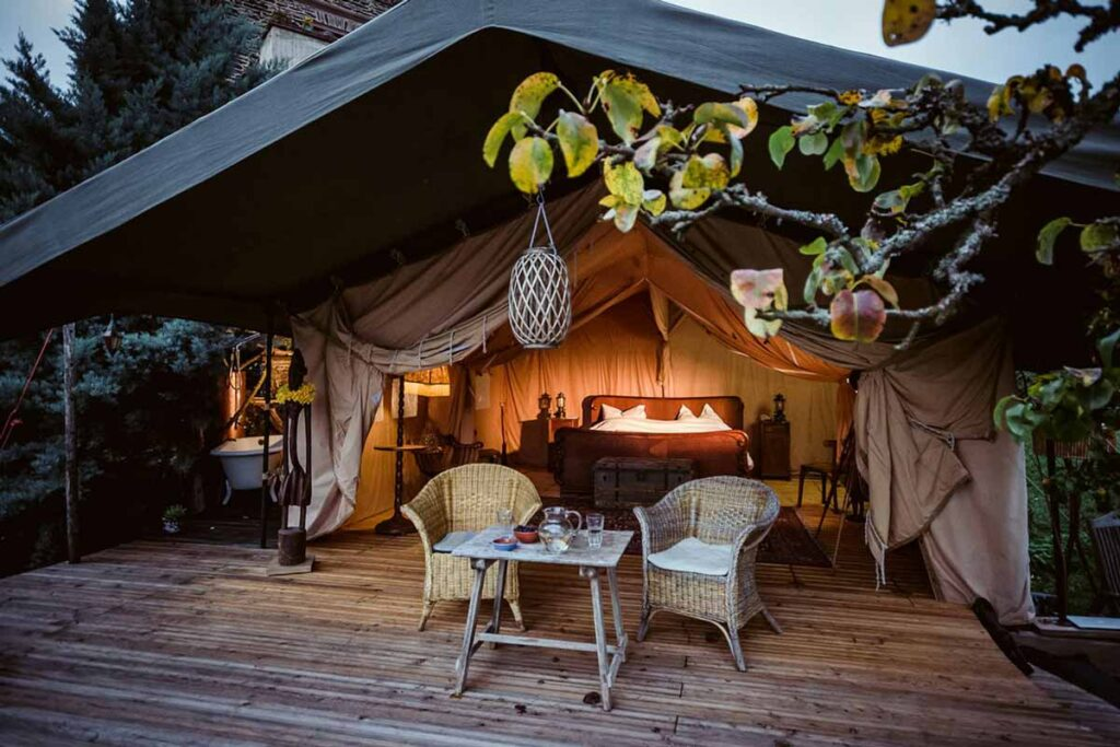 The inside of a glamping tent by the Glampinghub blog featuring a double bed, handers and two chairs on a patio in front.