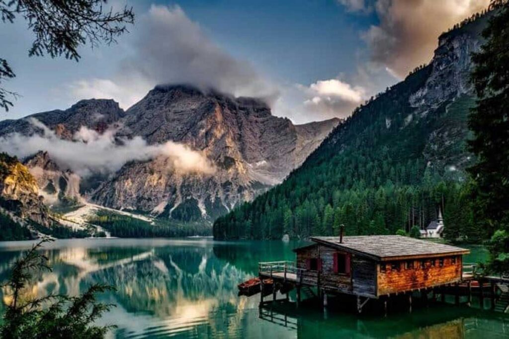 Glamping cabin set amongst a beautiful valley scene in front of a turquoise lake