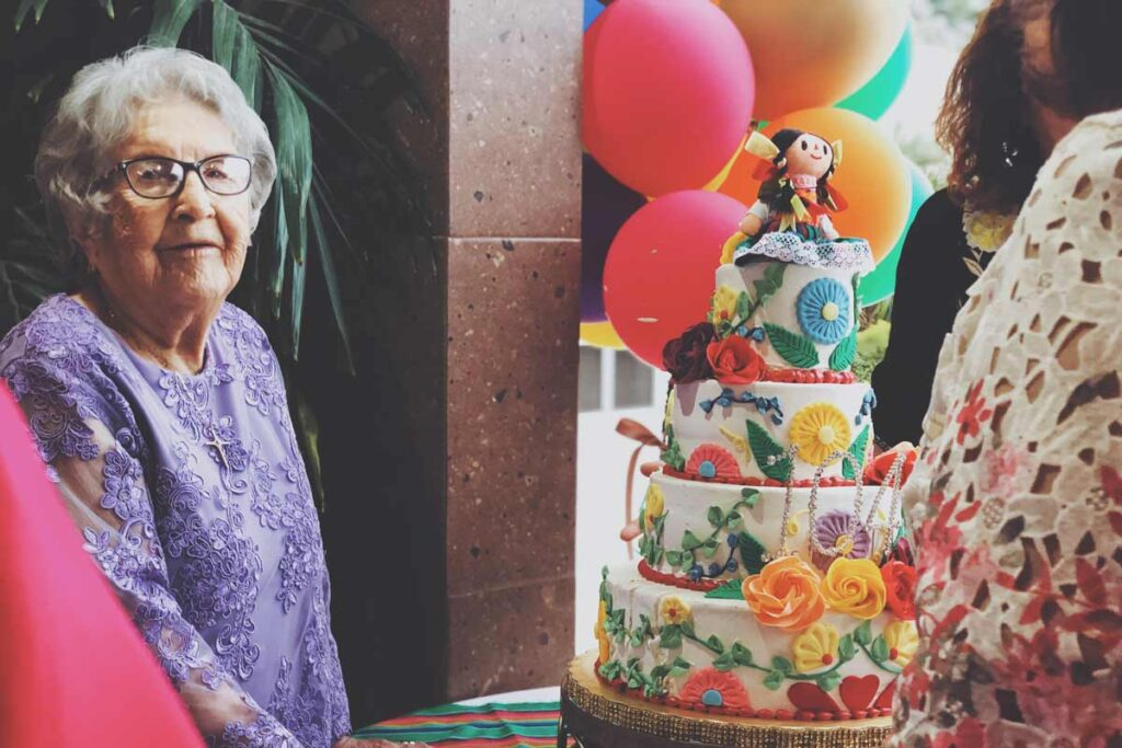 An old lady in front of her 100th birthday cake