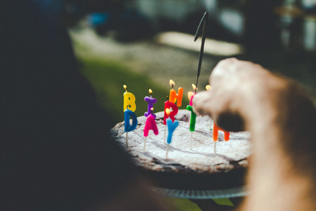A man lights the Happy Birthday candles on a cake