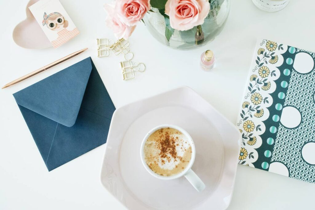 A birthday card lies on the table with coffee and roses while what to write in it is considered