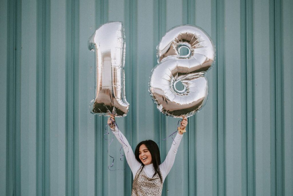 On her milestone birthday a girl holds up 18 balloons