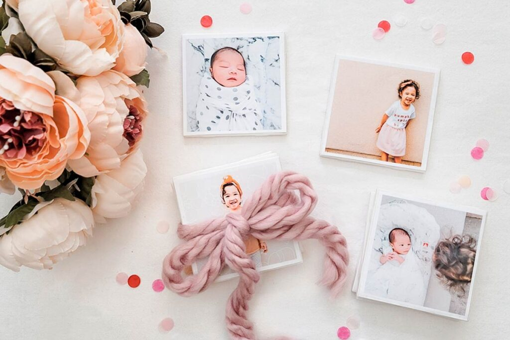 Homemade DIY photo coasters gift idea lying next to flowers, and decorated with a ribbon.