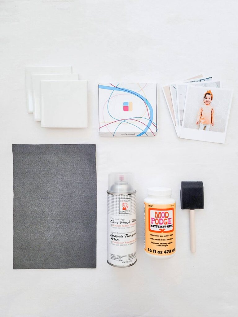 The materials for a DIY photo coaster on a white background: grey felt, a pack of prints, a photo, Mod Podge, a brush, spay and the ceramic tiles.