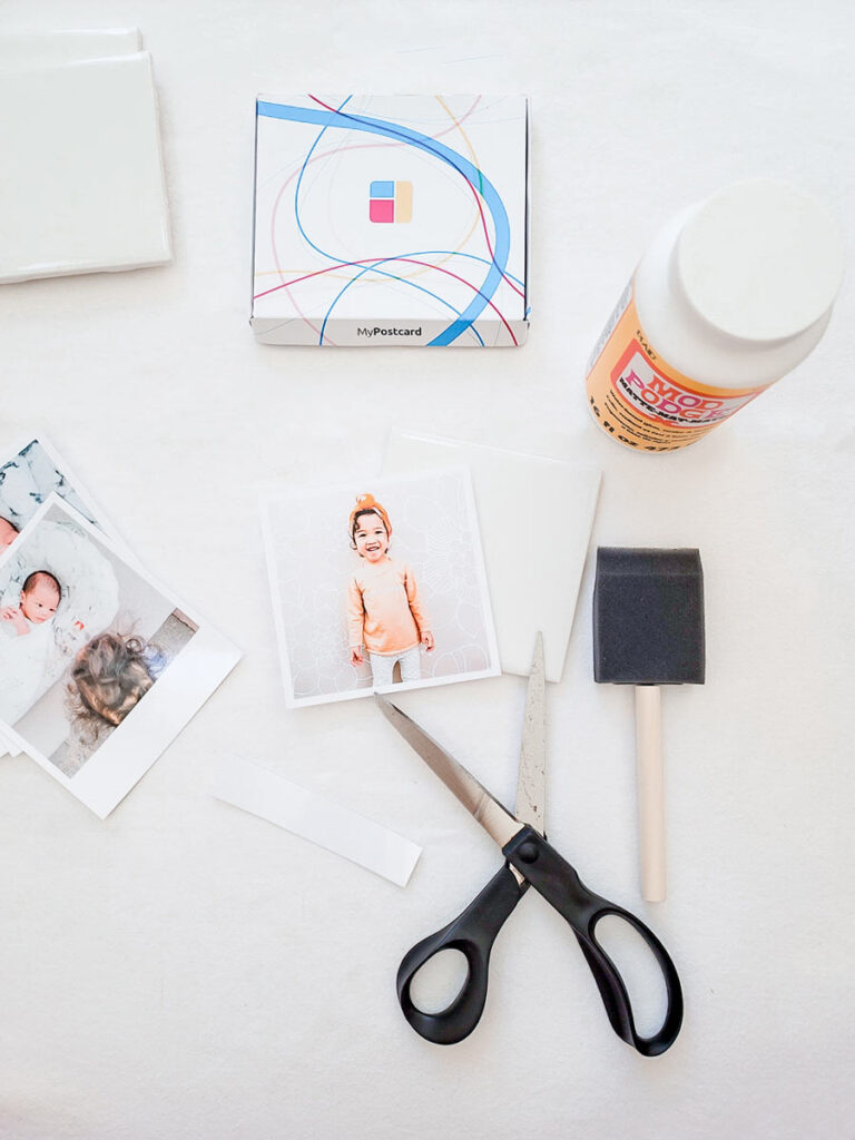 Scissors next to a cut out photo surrounded by the materials for the DIY coaster: a ceramic tile, more MyPostcard photos, Mod Podge and a brush.