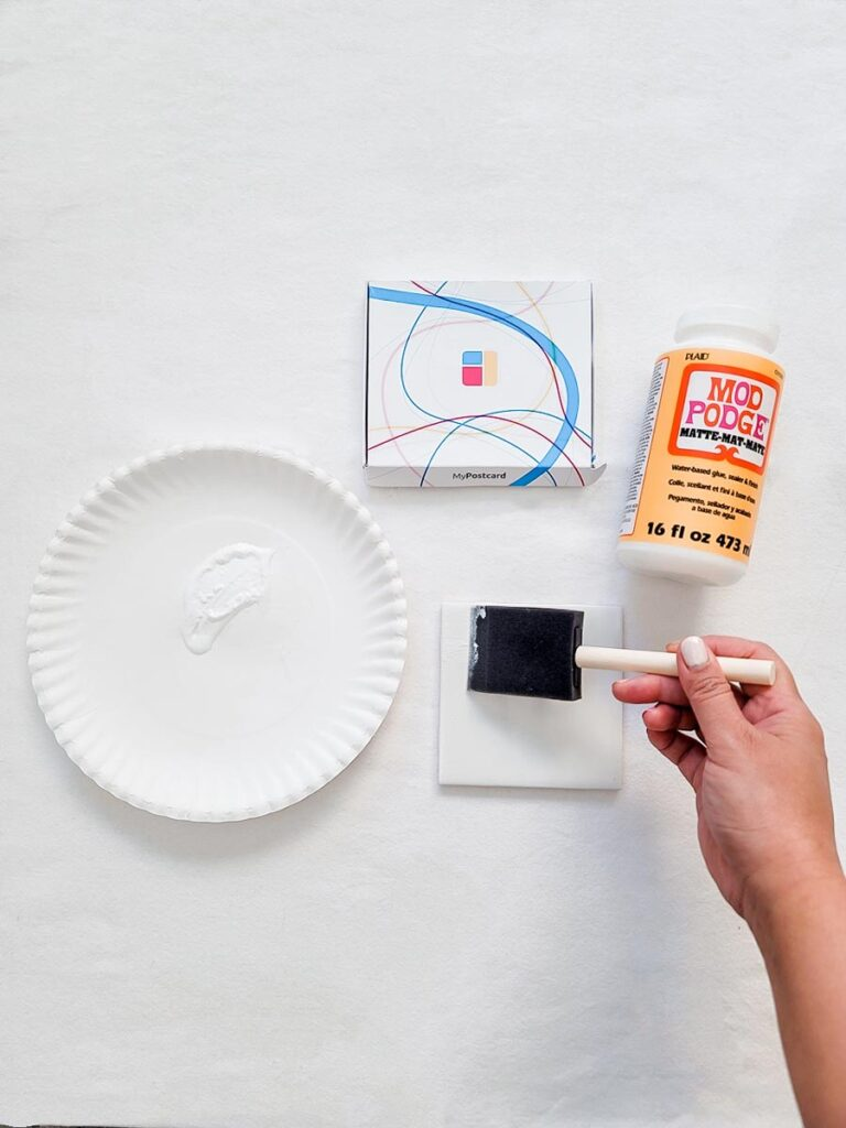 A brush paints the Mod Podge on to the ceramic tile. Next to the tile are the photo prints ready, a plate with the glue and the packet.