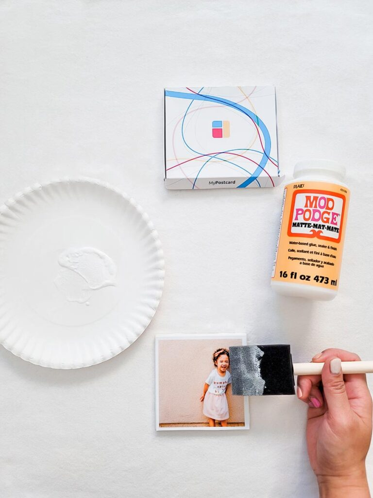 A photo print of a little girl stuck onto the tile with a brush painting a layer of mod podge on top. A paper plate, the print packet and the mod podge packet are also visible on a white background.