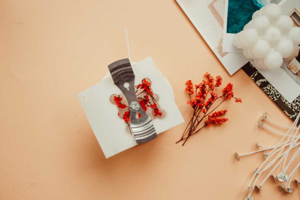 Dried flowers like next to and inside the silicone candle cast. To the side of the apricot flatlay, is a readymade bubble candle lying atop photo prints.