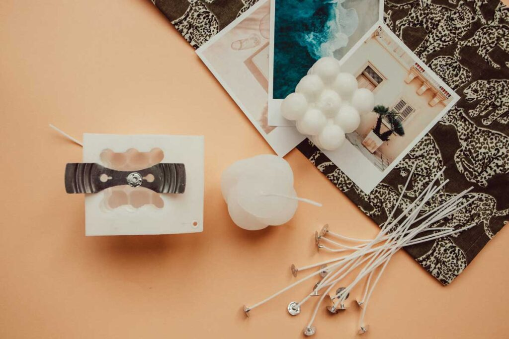 The wick is places in the silicone cast. More wicks lie on the apricot background next to two readymade bubble candles which lie on top of photo prints.