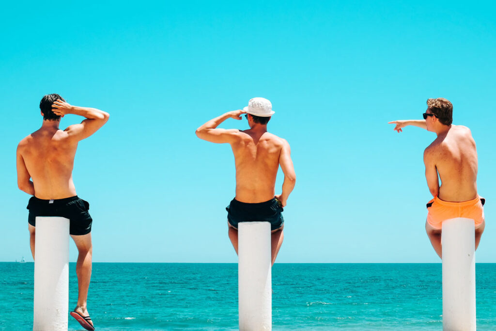 Three boys sit with their backs to the camera on white poles on a beach in Australia under blue skies.