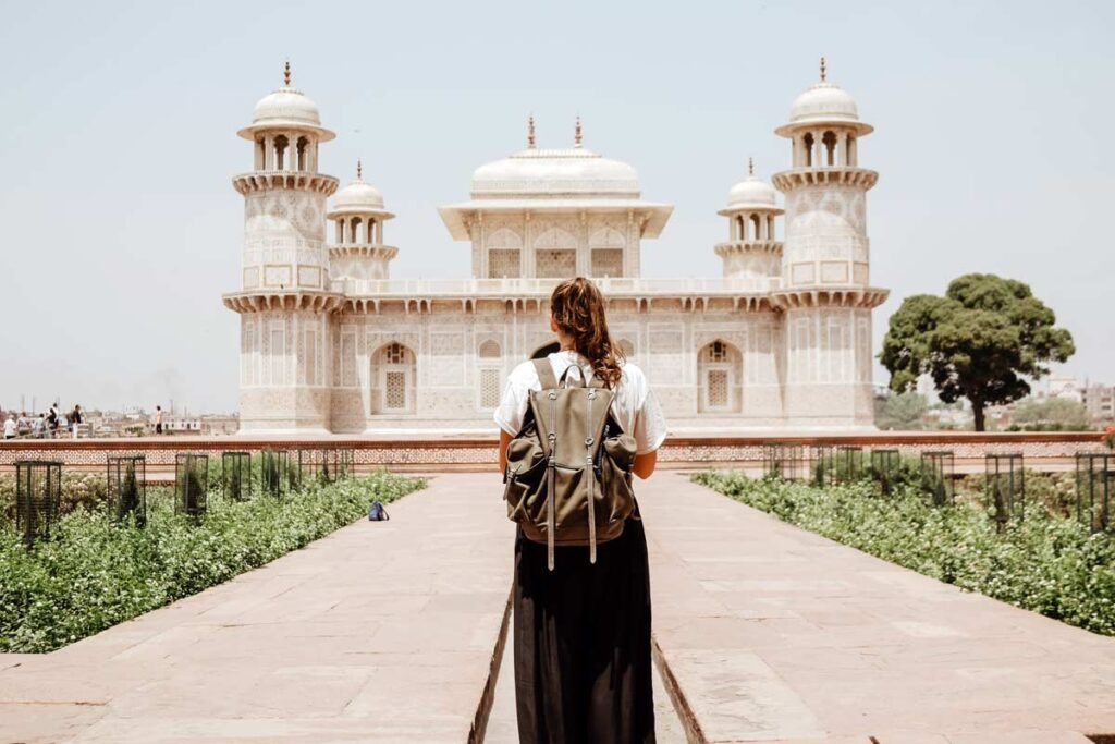 A woman with a backpack on walks towards the Taj Mahal in India