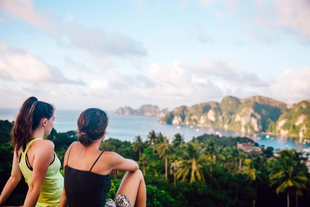 Two girls sit looking out at their gap year destination in Thailand, the sea surrounded by cliffs