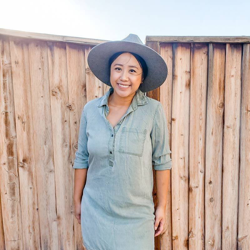 DIY author, Melody stands in front of a wooden fence in a hat and a blue dress.