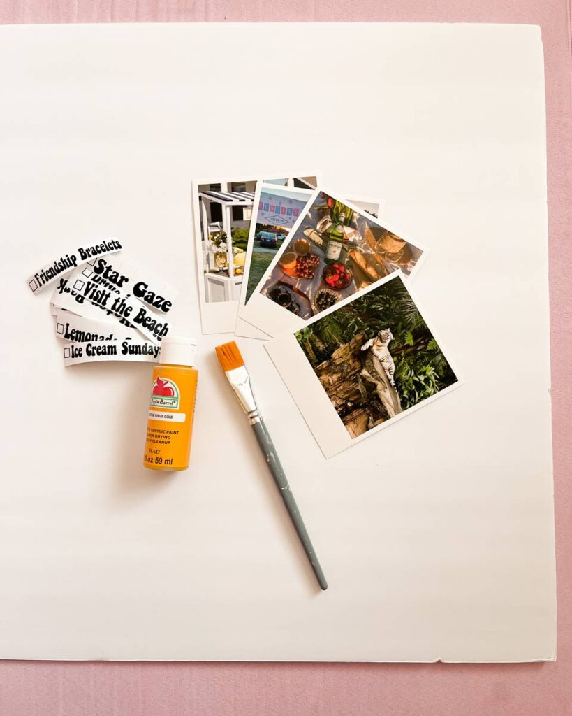 Photo prints lie on a white paper, next to glue, letter stickers and a paintbrush.