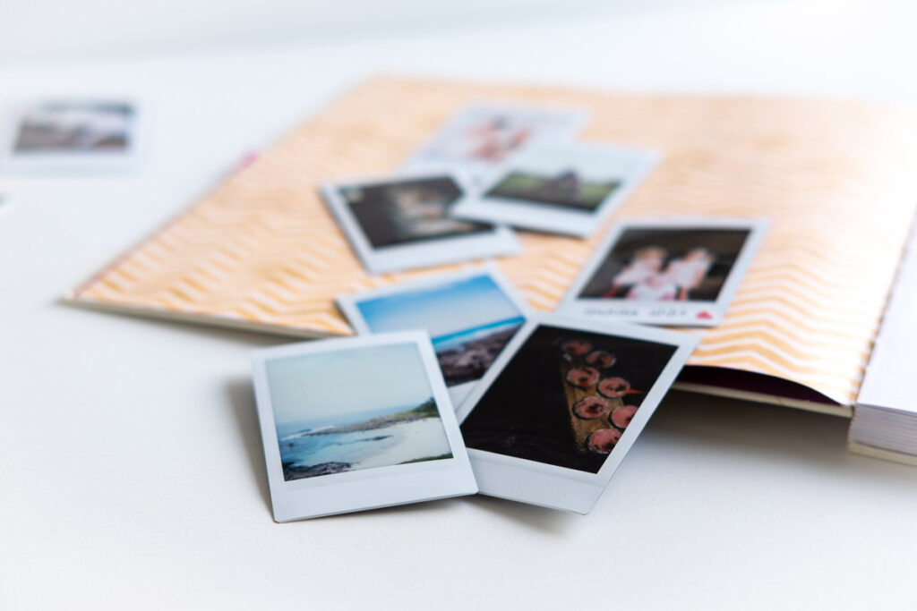 Instant prints on lying scattered on top of a yellow zebra-striped page of a book.