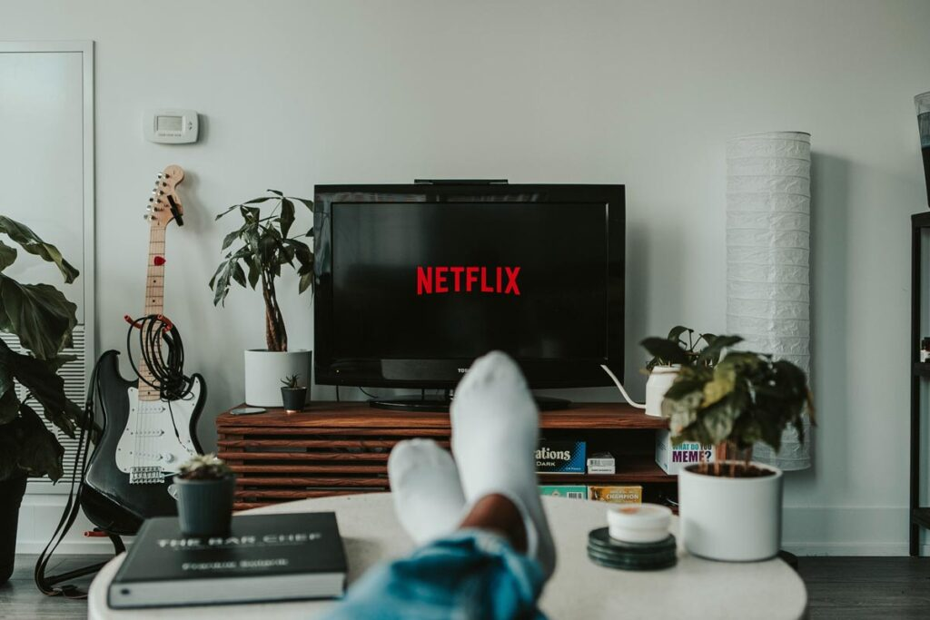 A view of Netflix on the TV with feet stretched out in front of the camera