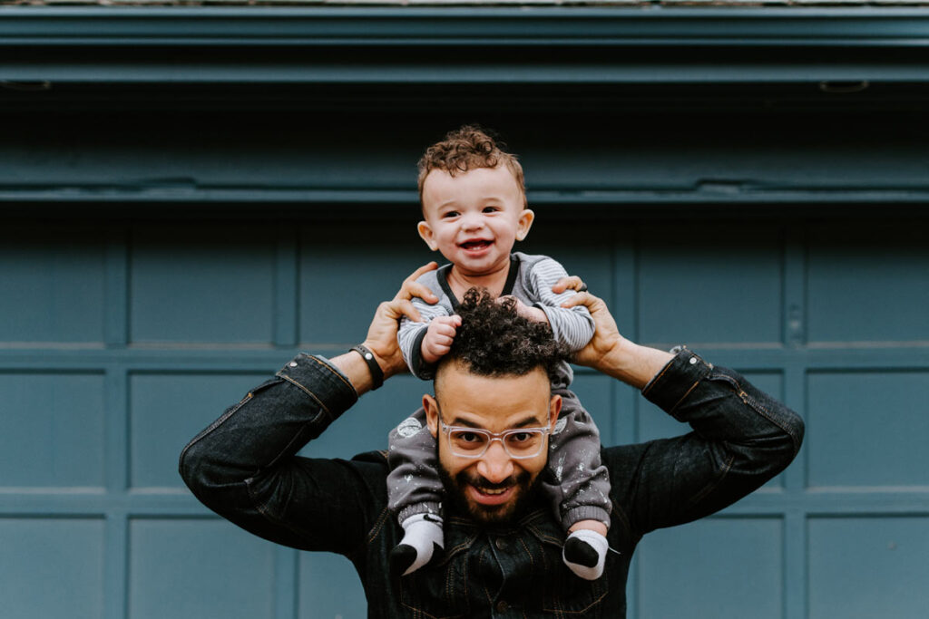 A man with his toddler sitting on his shoulders in front of a teal blue garage