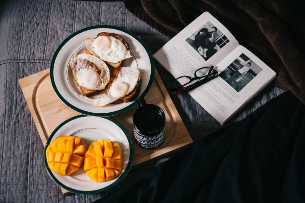 A bird's eye view of a brunch with egg and mango on two plates, a cup of coffee and a book with glasses on top.