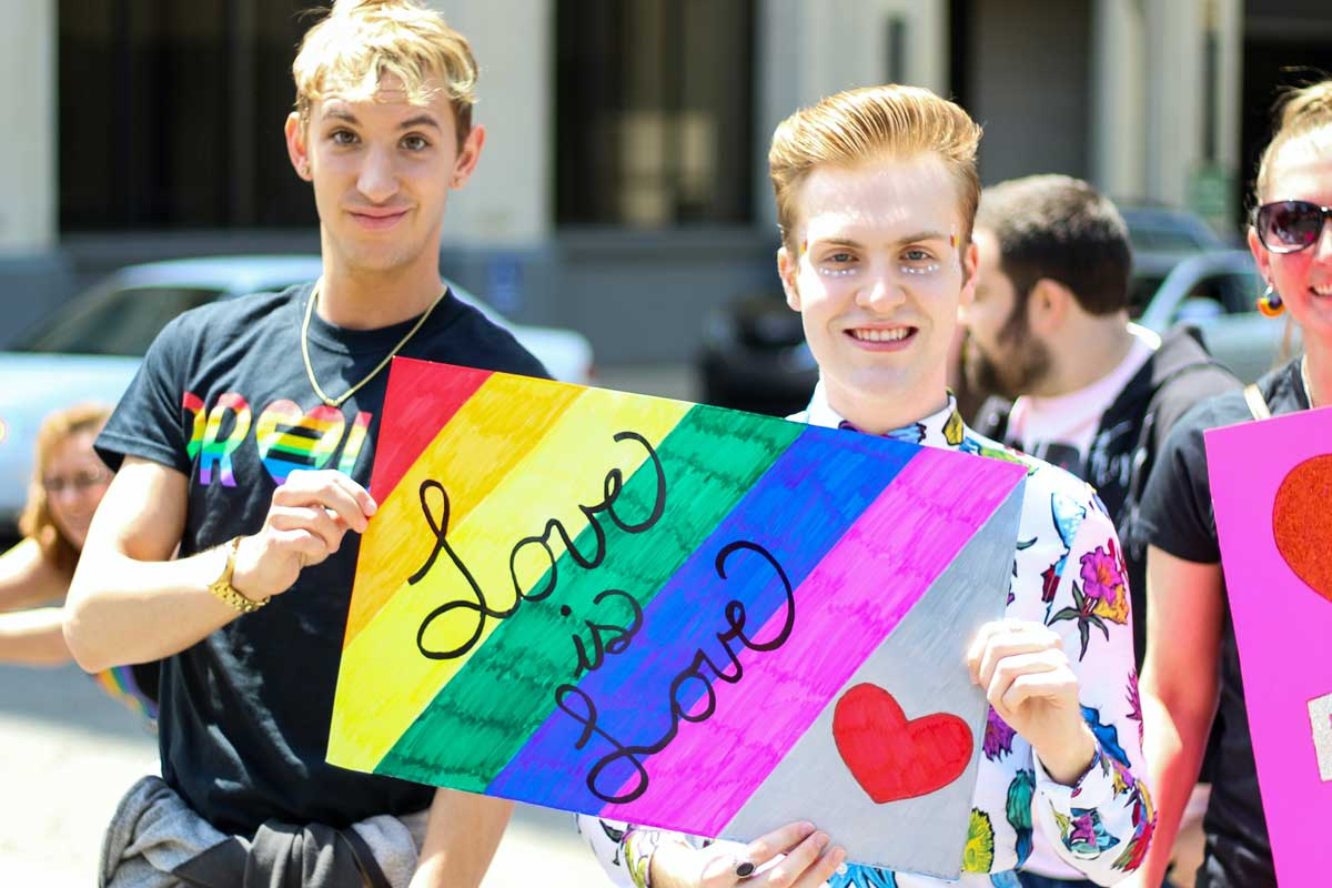 Two male-presenting people hold up a rainbow colored card saying 'Love is love'
