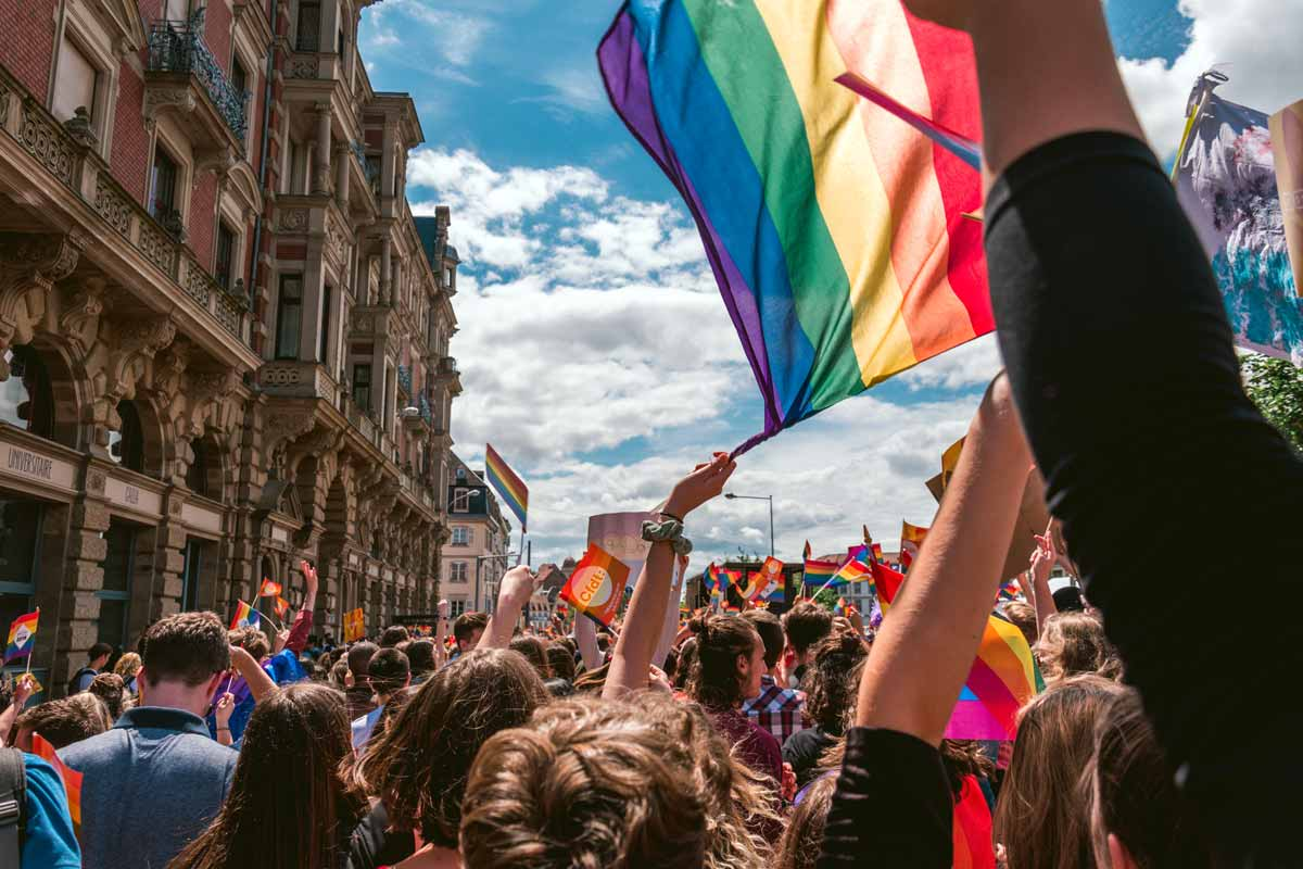 A gay pride procession in France through the streets with one rainbow flag held high