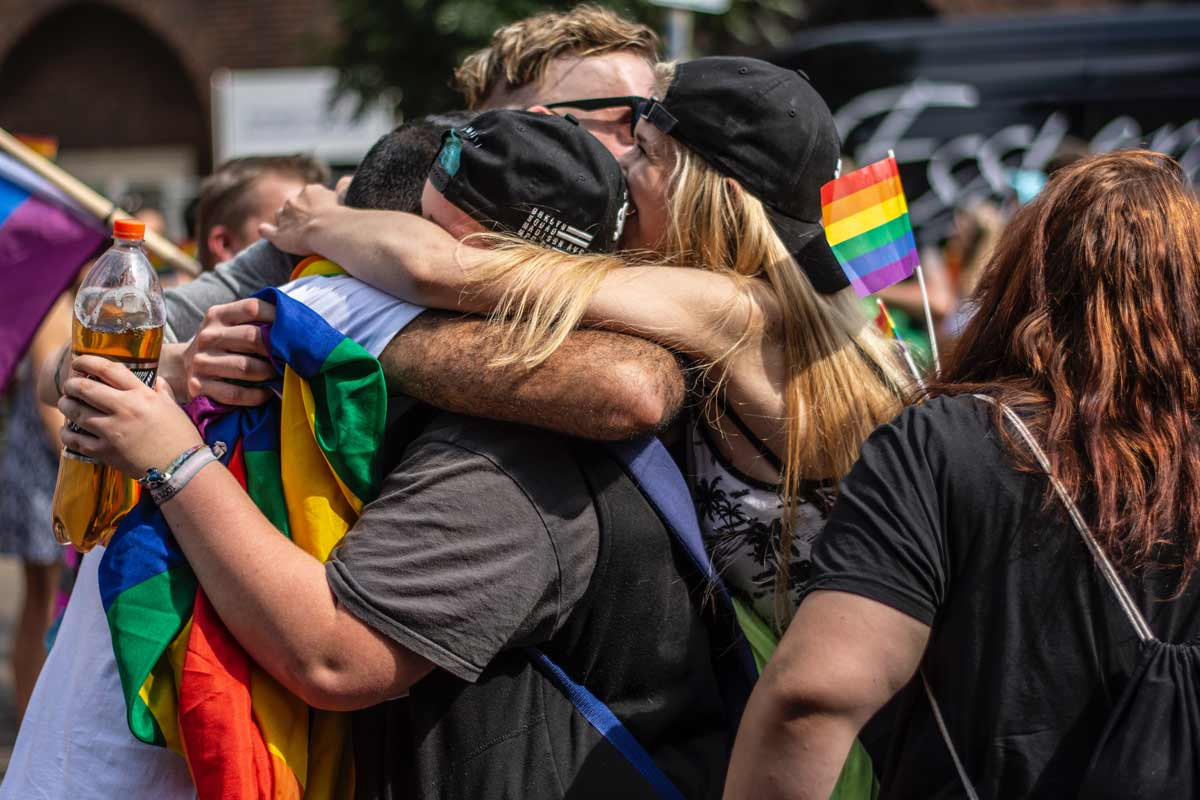People at a Pride Month celebration hugging in a group. Some hold small rainbow flags.