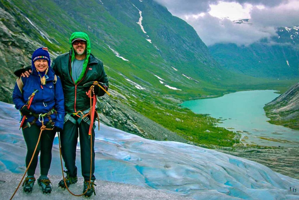 Two sustainable travel influencers stand with their arms around each other in front of a green valley, with a river winding through it.
