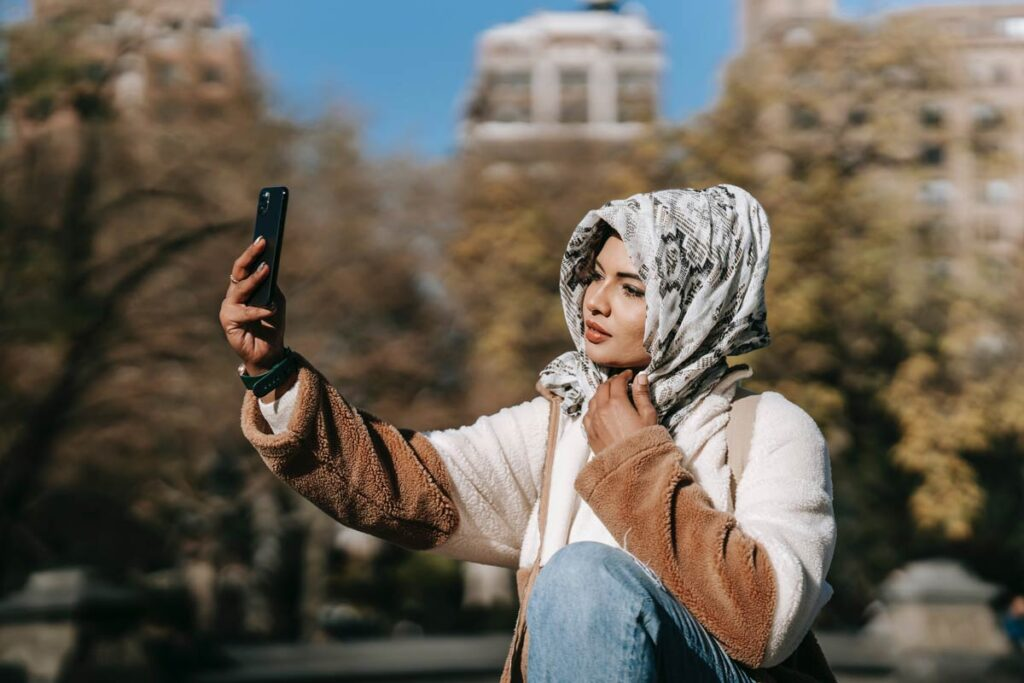 A woman takes a sexy selfie using a mouth slightly open pose. She is standing outside in a cityscape.