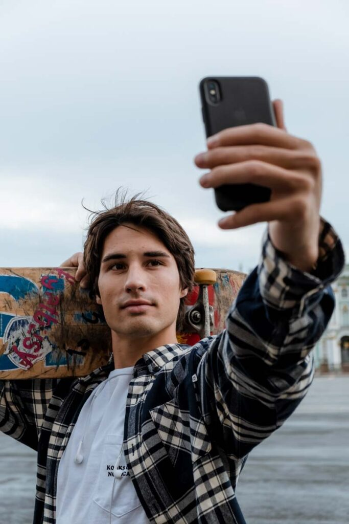 A man holding a phone takes a sexy selfie posing with a skate board held behind him.