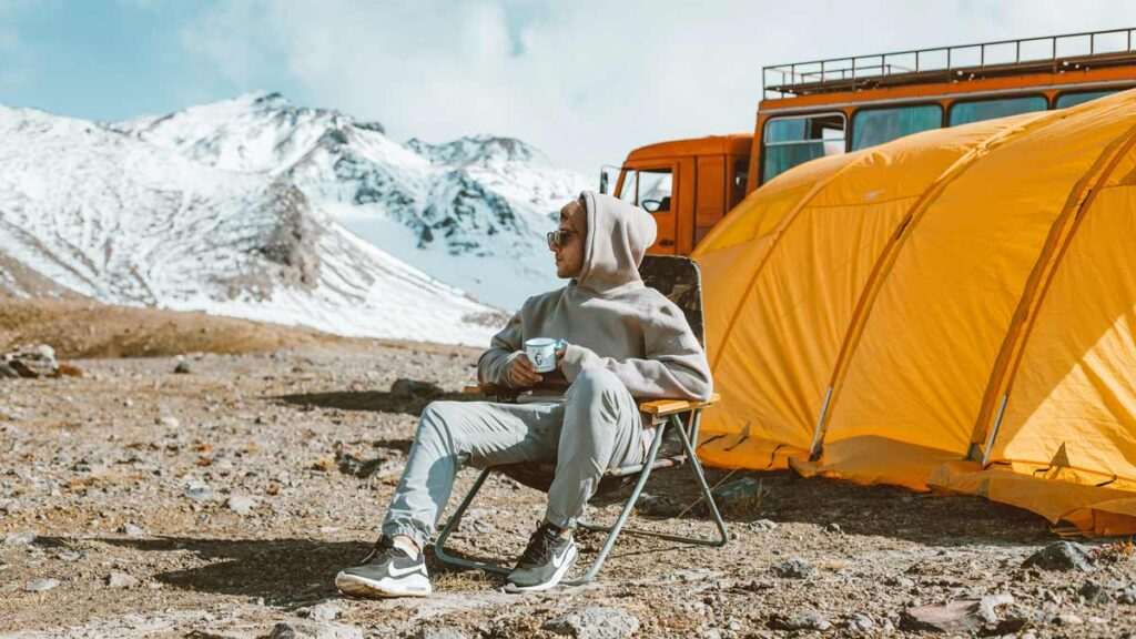A man sits on a camping chair in front of a yellow tint next to the snowy mountains.