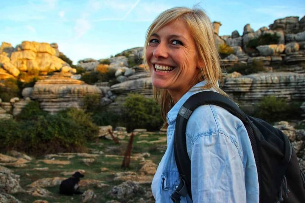One of the top sustainable travel bloggers, Linn Hagland smiled over her shoulder at the camera, standing in a rocky landscape.