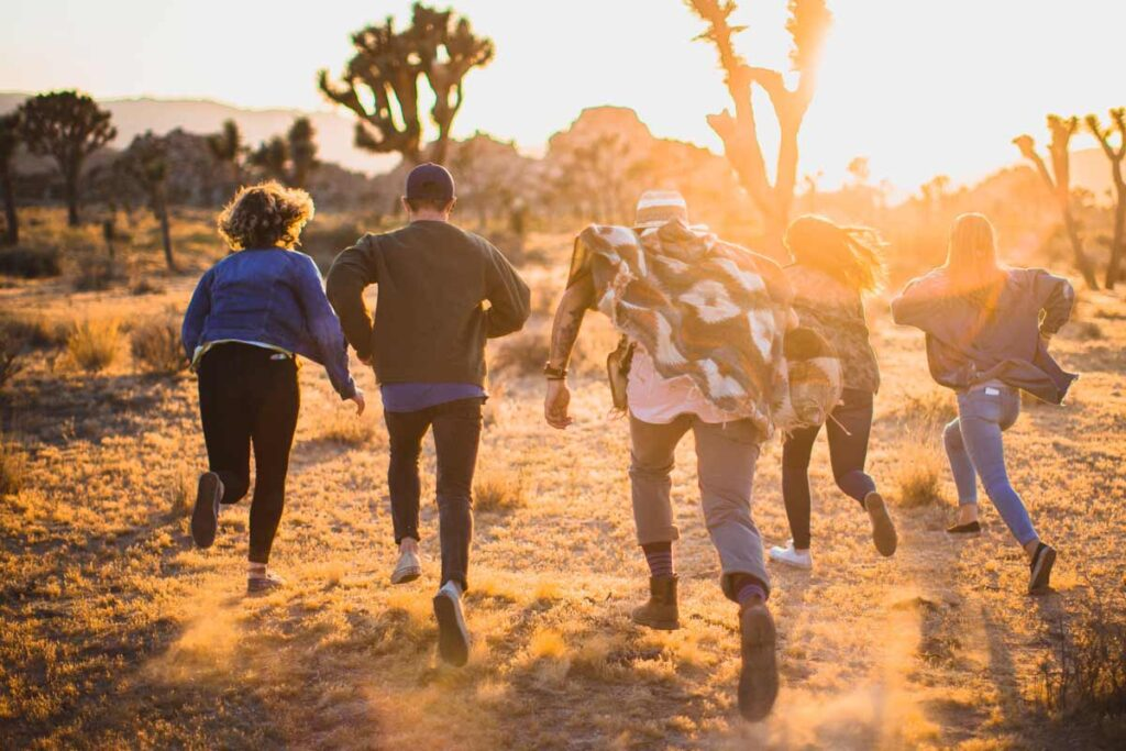 4 young people running into the sunset in a safari landscape