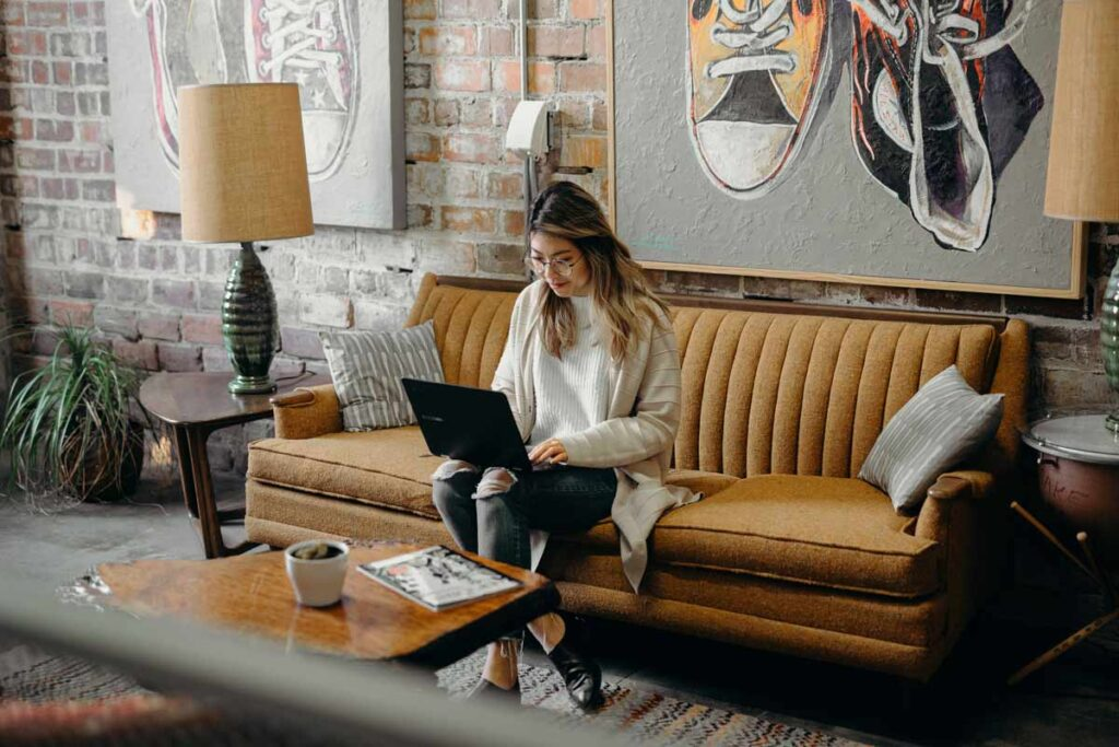 A young woman sits on a sofa in a cafe researching on her laptop
