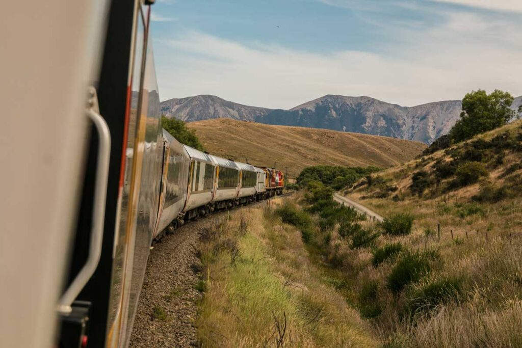 A train slides through the picture and through rolling hills in an open green landscape