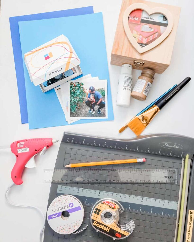 The materials for the DIY photo box lie on a table - glue gun to paintbrush and photos