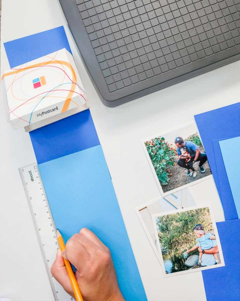Photos resting next to cut blue paper while a hand and ruler measures out where to put them
