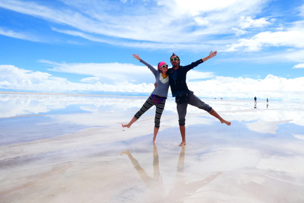 A man and a woman stand together with one arm and one leg in the air to form a starfish. They're standing in front of the salt flats.