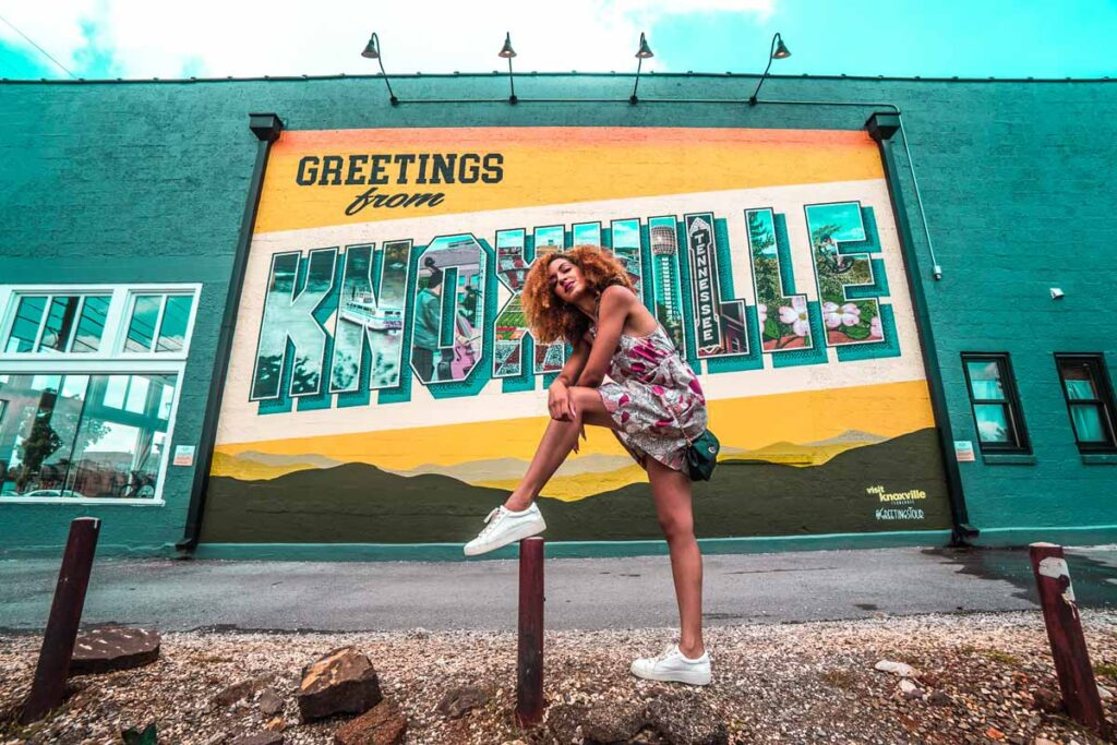 A woman has her foot on top of a pole and poses crouching down. The camera looks up at her and a big 'greetings from Knoxville' sign.