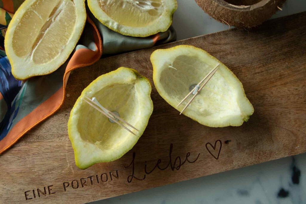 4 lemon shells on the wooden board, in two of them a wick held in place by tooth picks in the empty lemon halves.