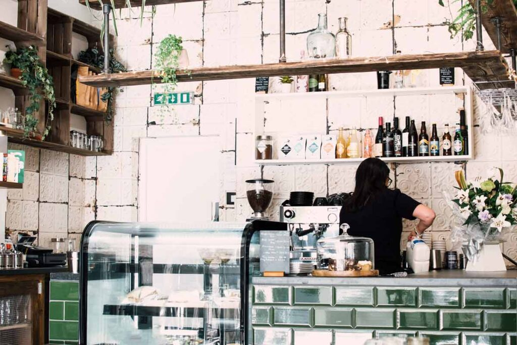 A barista works in one of the best coffee spots in London, featured behind the counter