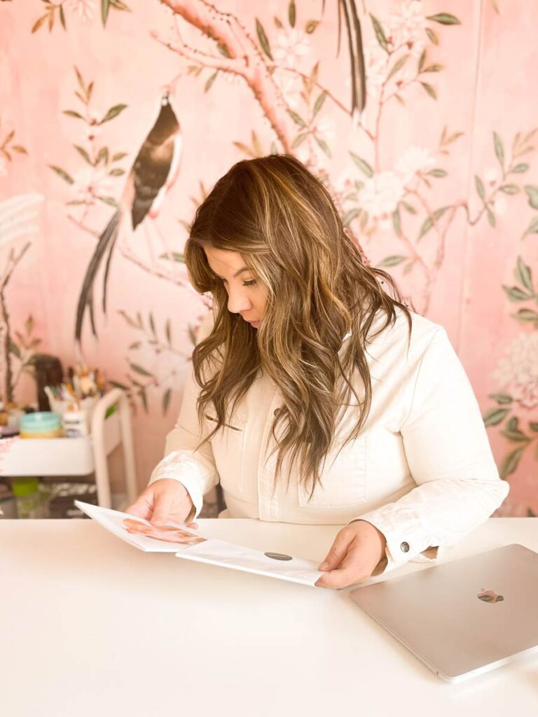 Katelyn sitting in a pink room unpacking the photobook