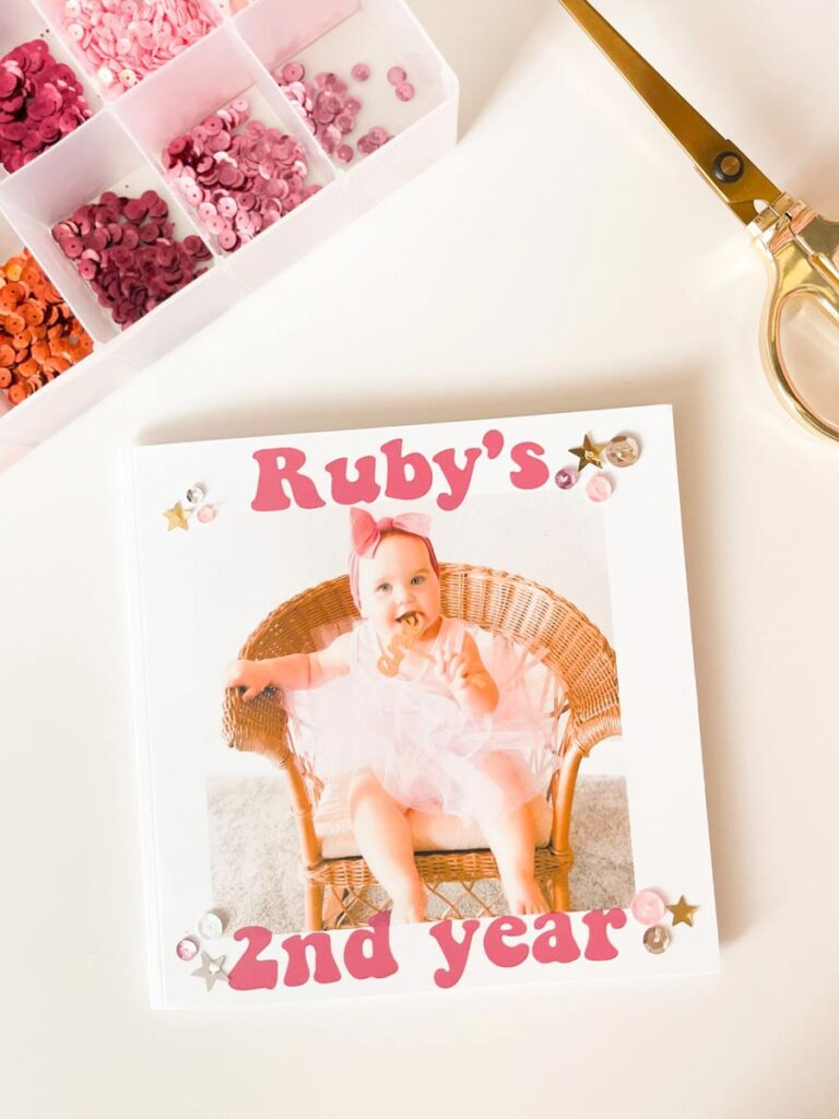 A box of sequins and sparkles next to the DIY photo yearbook.