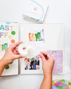 Double sided tape being used to stick photos into the photobook